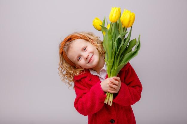 Un enfant une fille blonde tenant un bouquet de tulipes jaunes