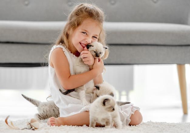 Enfant fille caresser les chatons ragdoll et souriant. petite personne de sexe féminin heureuse avec des animaux de compagnie à la maison