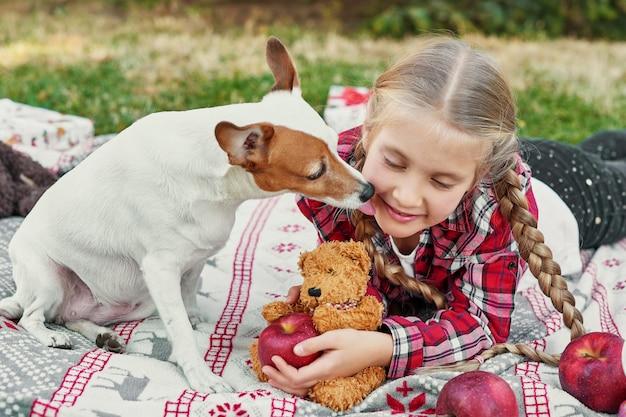 Enfant fille avec chien jack russell terrier près de l'arbre de noël avec des cadeaux,