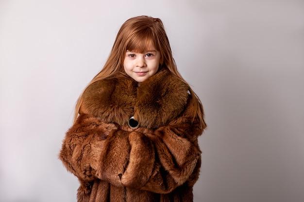 Un enfant, une fille dans le manteau de fourrure de sa mère. fausse fourrure, vêtements d'hiver, manteaux de fourrure grande taille pour enfant