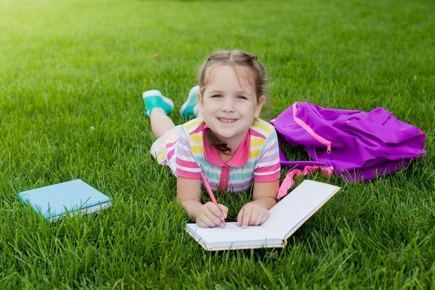 Enfant fille écolière élève du primaire couché sur l'herbe et dessine dans un cahier.