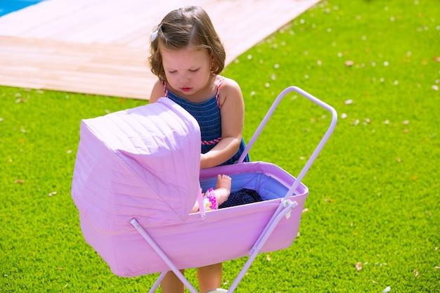 Enfant fille enfant jouant avec bébé panier en vert gazon