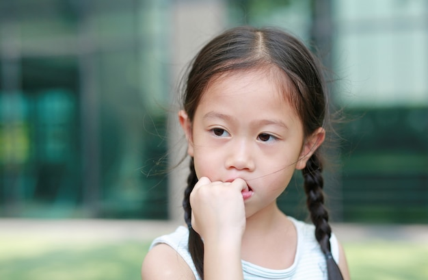 Enfant fille a l'intention de sucer ses doigts. les gestes d'enfants qui manquent de confiance en soi.