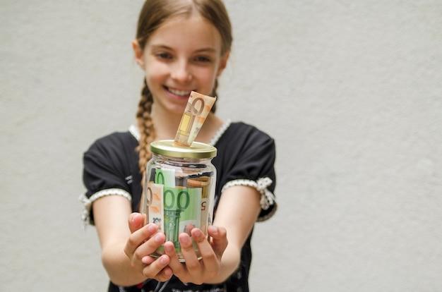 Enfant fille mains tenant le pot de verre plein de billets d'argent et sourire