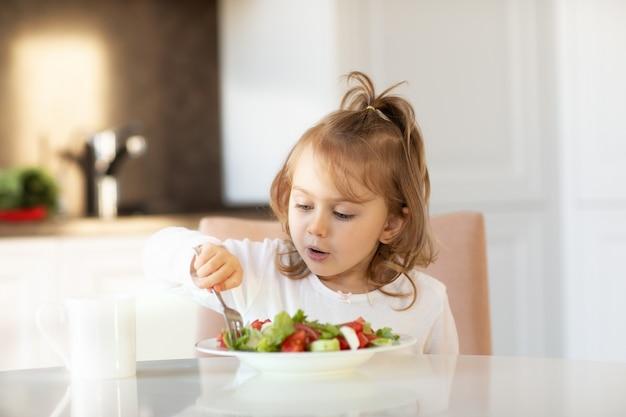 Enfant fille mangeant une salade de légumes frais à l'intérieur assis à table de cuisine