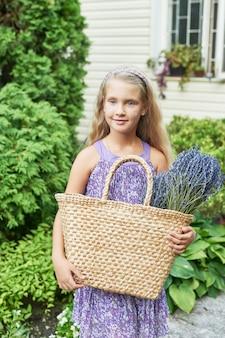 Enfant fille avec un panier de lavande dans le jardin en été