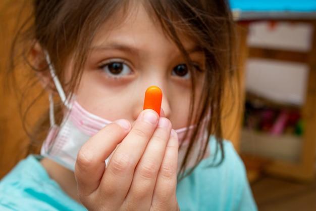 Enfant fille portant un masque de protection médical avec une pilule dans une main à la maison pendant l'isolement en quarantaine