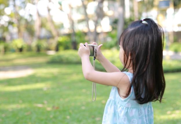 Enfant fille prenant des photos sur l'appareil photo dans le jardin