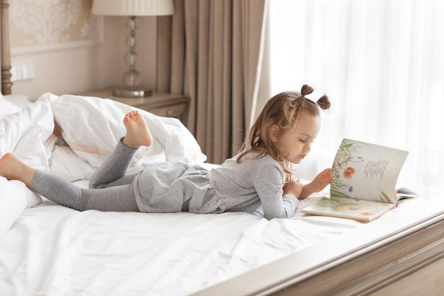 Enfant fille se détendre et lire des histoires de livres intéressantes dans un lit confortable le matin près de la fenêtre.confort, concept de maison confortable