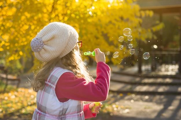 Enfant fille soufflant des bulles de savon