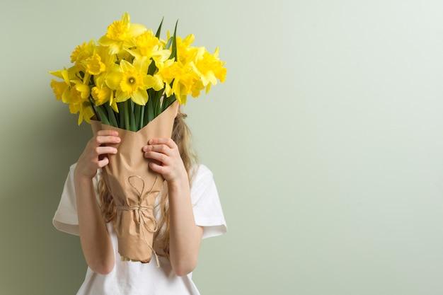 Enfant fille tenant le bouquet de fleurs jaunes.