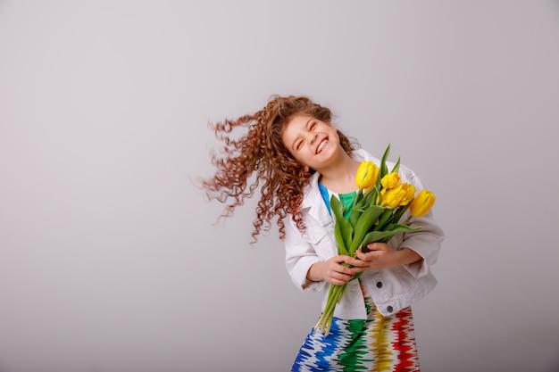 Un enfant une fille tenant un bouquet de tulipes jaunes