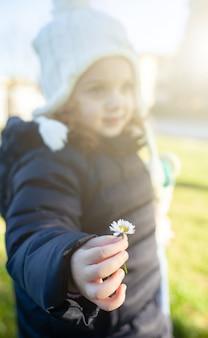 Enfant fille tenant une fleur de marguerite.