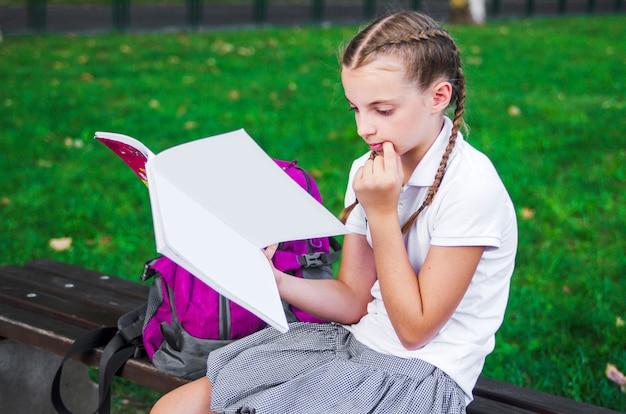 Enfant fille en uniforme assis et lisant un livre, apprennent les devoirs sur le banc de la cour d'école