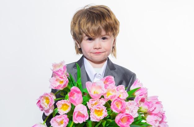 Enfant avec des fleurs. petit garçon avec des tulipes. cadeau à la mère. journée de la femme, fête des mères, saint valentin.