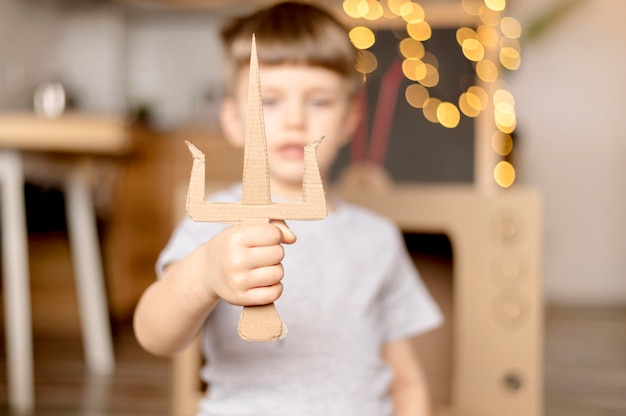Enfant flou avec poignard en carton