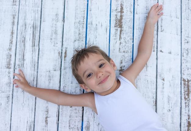 Enfant sur un fond en bois blanc