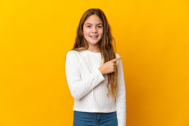 Enfant sur fond jaune isolé pointant sur le côté pour présenter un produit