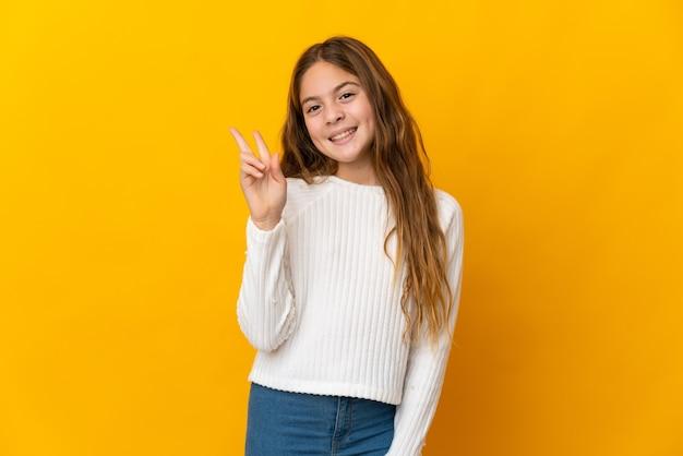 Enfant sur fond jaune isolé souriant et montrant le signe de la victoire