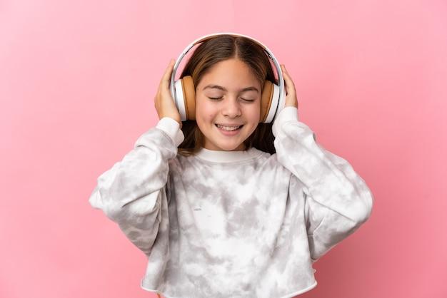 Enfant sur fond rose isolé écouter de la musique