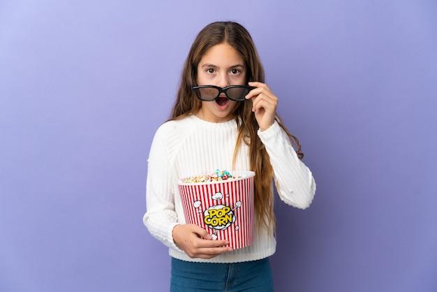 Enfant sur fond violet isolé surpris avec des lunettes 3d et tenant un grand seau de pop-corn