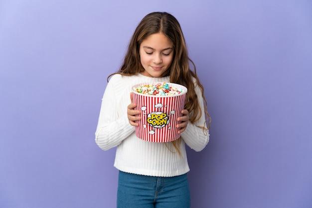 Enfant sur fond violet isolé tenant un gros seau de pop-corn