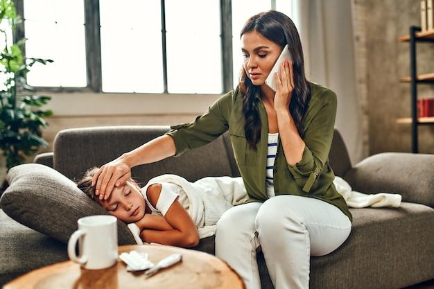 L'enfant a une forte fièvre. maman touche le front de sa fille et appelle une ambulance. la petite fille est tombée malade.