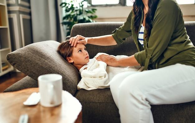L'enfant a une forte fièvre. maman touche le front de sa fille, qui est allongée sous les couvertures sur le canapé et est malade.