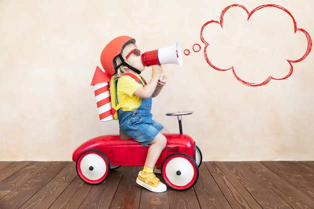 Enfant avec fusée en papier jouant à l'intérieur