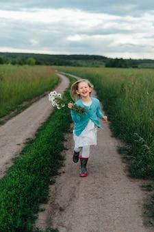 Un enfant gai qui court avec un bouquet de marguerites en bottes