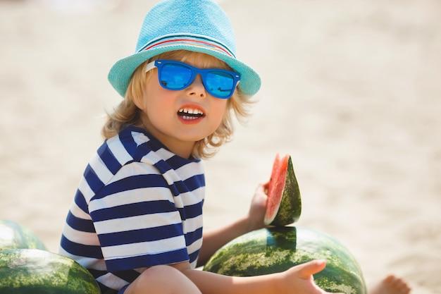 Enfant gai souriant avec pastèque sur le bord de mer. joli petit garçon sur la plage, manger de la pastèque. enfant souriant heureux.