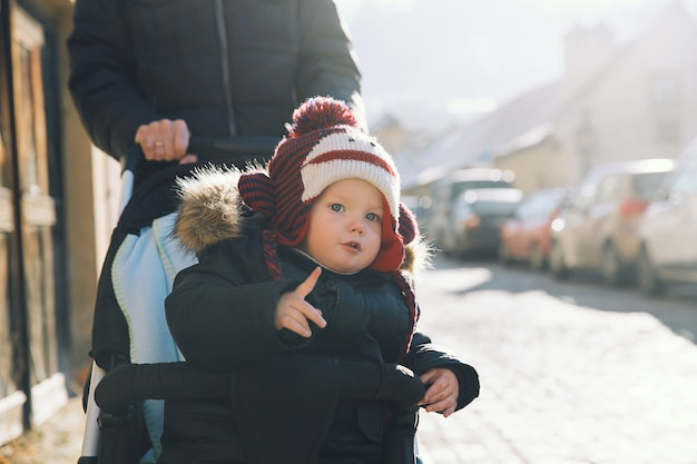 Enfant garçon dans un chapeau drôle en poussette passer des vacances d'hiver en famille au marché de noël à cesky krumlov, république tchèque, europe.