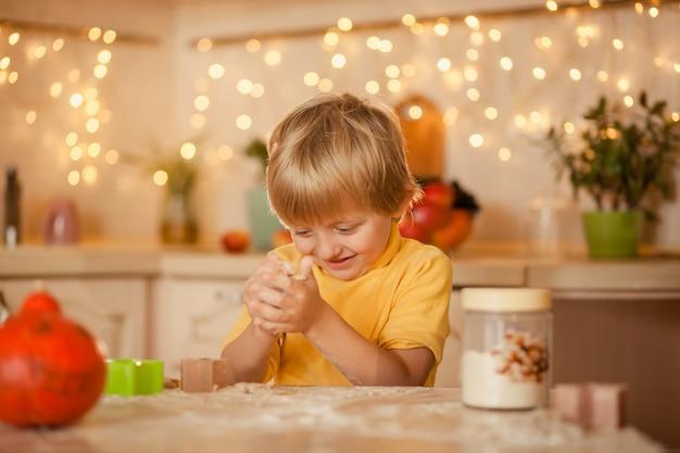 Enfant garçon dans la cuisine à la table jouant avec de la farine