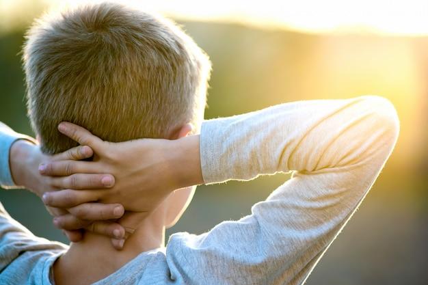 Enfant garçon debout à l'extérieur par une journée ensoleillée d'été bénéficiant d'un temps chaud à l'extérieur. concept de repos et de bien-être.