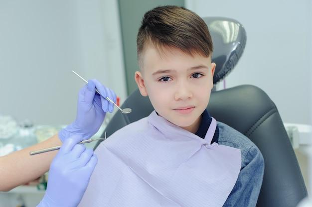 Un enfant garçon avec un dentiste dans un cabinet dentaire