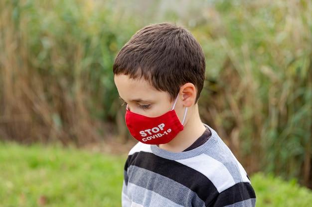 Enfant garçon ennuyé et triste avec masque facial se sentant déprimé