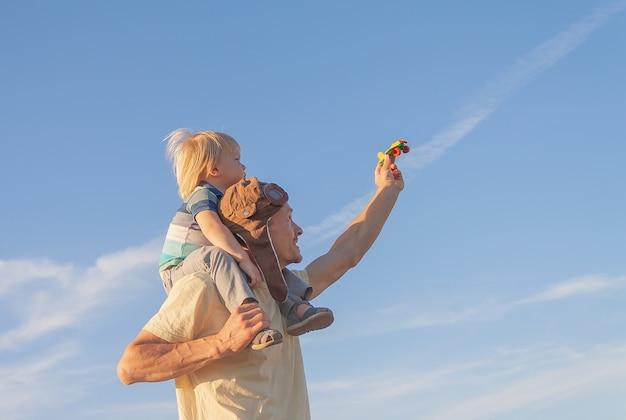 Enfant garçon sur les épaules du père avec jouet avion. papa et fils jouant avec un avion jouet à l'extérieur