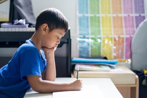Enfant garçon est en train d'écrire un livre dans la chambre.