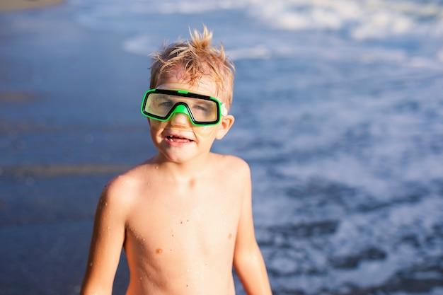 Enfant garçon jouant dans les vagues sur la plage au coucher du soleil de l'été, enfant regardant les vagues et s'amuser