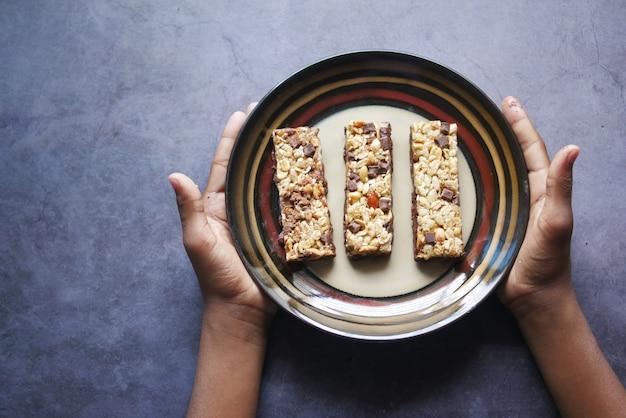 Enfant garçon main tenir une assiette de barres protéinées au chocolat aux amandes et à l'avoine