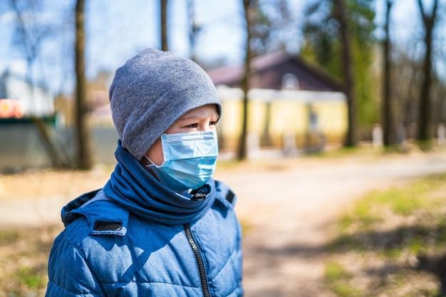 Enfant garçon marchant en plein air avec masque facial pour la protection