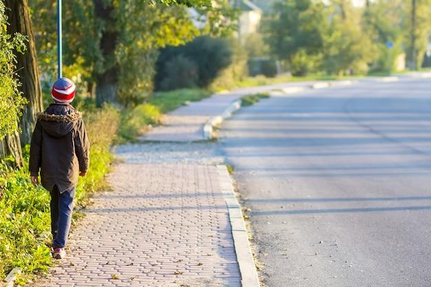Enfant garçon marchant seul sur un trottoir