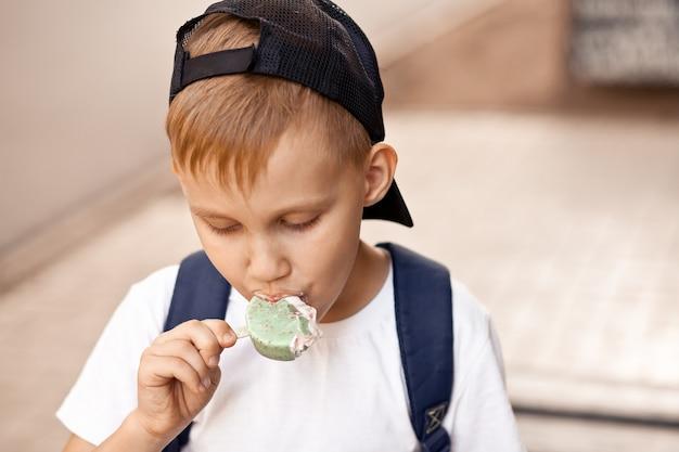 Enfant garçon mignon enfant mangeant des glaces en plein air dans un parc.