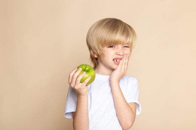 Enfant garçon mignon tenant une pomme verte en t-shirt blanc sur rose