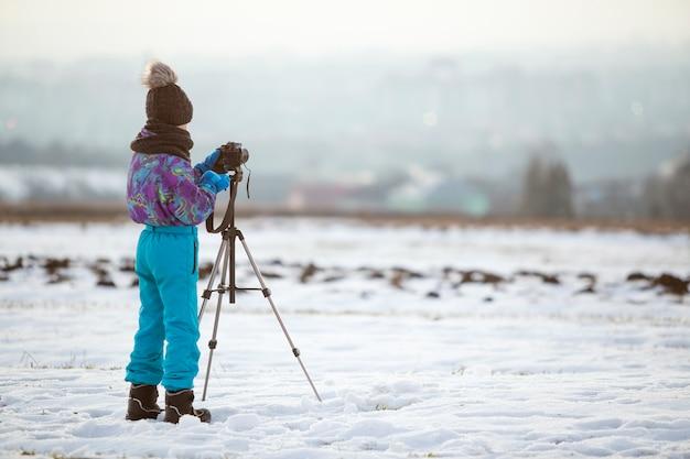Enfant garçon prenant des photos à l'extérieur en hiver avec un appareil photo sur un trépied sur un champ couvert de neige.