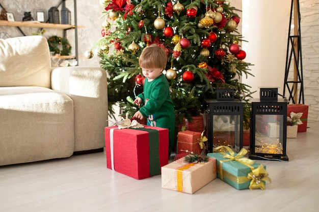 Enfant garçon s'amusant avec l'arbre de noël.