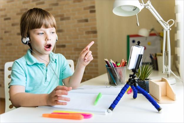 Enfant garçon utilise une tablette numérique pour un appel vidéo avec son professeur