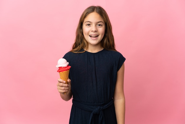 Enfant avec une glace au cornet sur fond rose isolé avec une expression faciale surprise