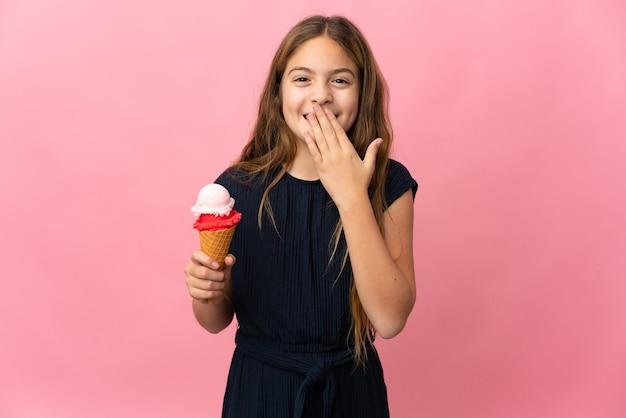 Enfant avec une glace au cornet sur fond rose isolé heureux et souriant couvrant la bouche avec la main