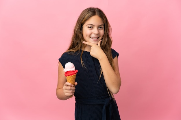 Enfant avec une glace au cornet sur fond rose isolé heureux et souriant
